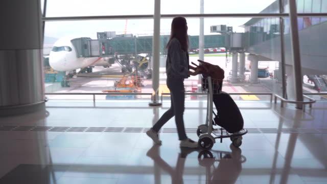 stockvideo's en b-roll-footage met passagiers in de luchtvaartmaatschappij liepen naar sleep de bagage naar de poort. in de passagiers zaal - tienermeisjes
