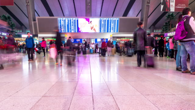 passengers in waiting hall of beijing station time lapse 4k - electronic billboard stock videos and b-roll footage