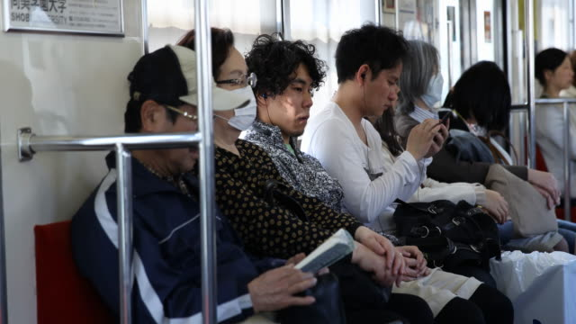 passengers inside the train in the public transportation of tokyo - surgical mask stock videos & royalty-free footage