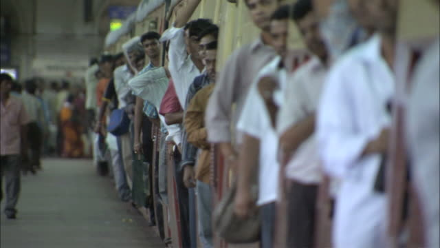 ms passengers leaning  out of doors of crowded train / mumbai, maharashtra, india - india video stock e b–roll