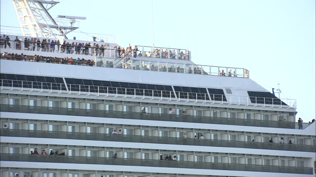 passengers line the rails of an enormous cruise ship. - cruise stock videos & royalty-free footage