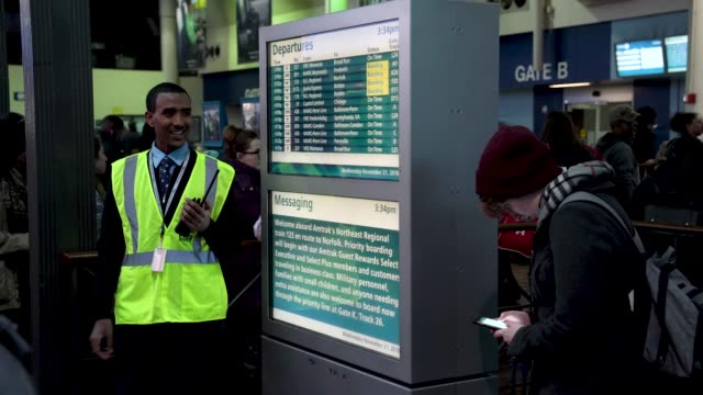 Passengers look at train information on an electronic bulletin board as they wait to board their trains at Union Station on the day before the...
