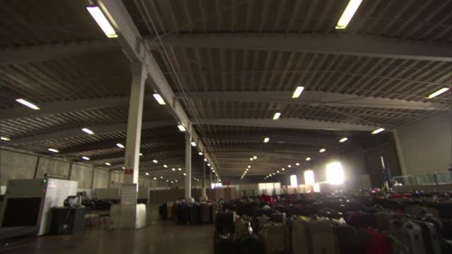 passengers' luggage fills a large hangar in san diego. - airplane hangar stock videos & royalty-free footage