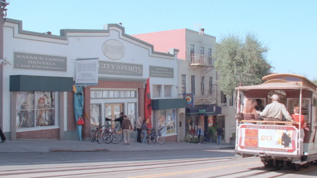 vídeos de stock, filmes e b-roll de passengers on  a cable car ride down a gentle hill in san francisco past a store called bay city sports. - cable