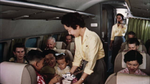 vidéos et rushes de passengers on a hawaiian airlines flight enjoy cool beverages, orchids, ukulele music, and hula lessons. - 1956