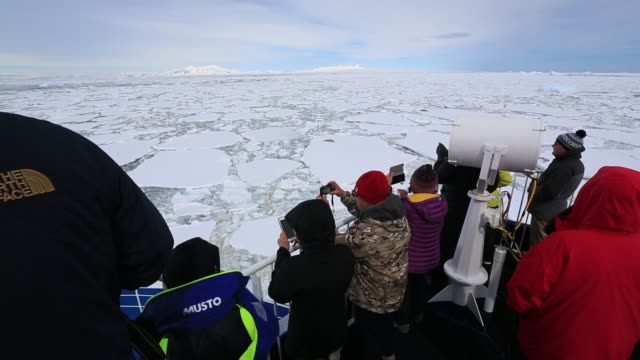 passengers on an antarctic cruise ship pushing through sea ice near crystal sound and the bisoce islands on they way to wards the polar circle - ice crystal stock videos and b-roll footage