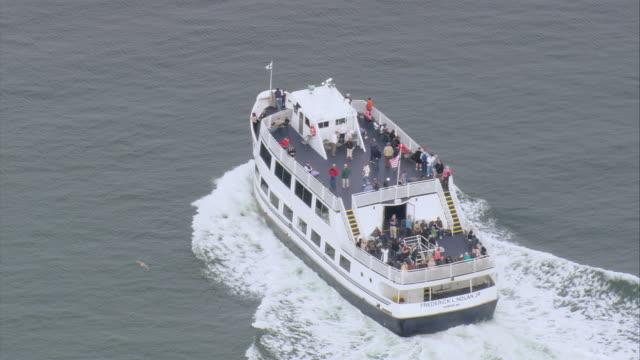 vídeos de stock, filmes e b-roll de aerial passengers on board the deck of ferry cruising through the water / boston, massachusetts, united states - passear sem destino