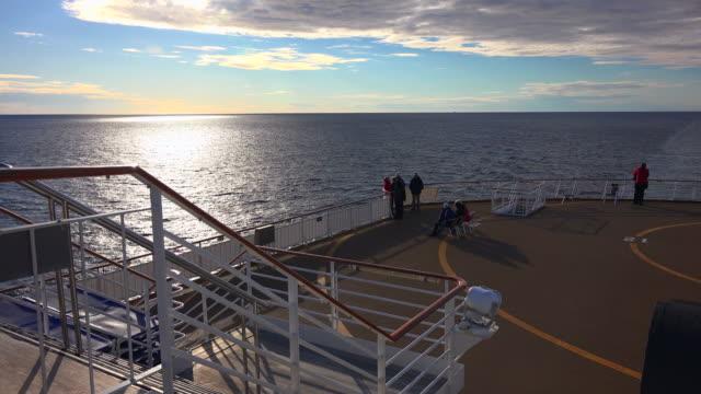 Passengers on cruise ship at sunset