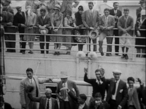 b/w 1924 pan passengers on deck of cruise ship wave to camera as it pulls from dock / newsreel - 1924 stock videos & royalty-free footage