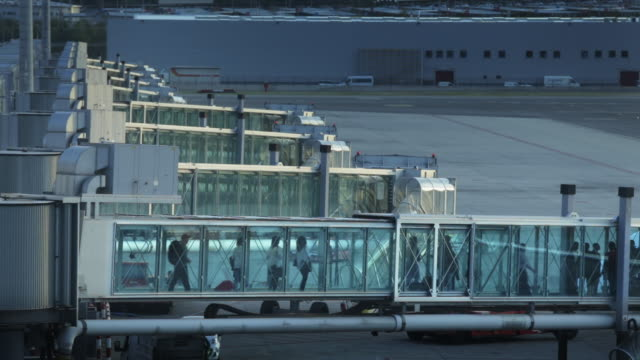 passengers on jetway at madrid barajas international airport. - imbarcarsi video stock e b–roll