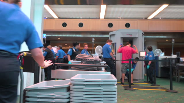 Passengers pass through metal detector and physical search by TSA at security checkpoint inside Portland International Airport