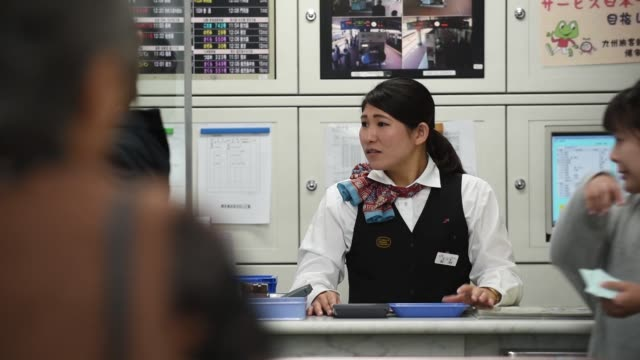 passengers pass through turnstiles at hakata station in fukuoka city, fukuoka prefecture, japan, on tuesday, oct 11 a kyushu railway co. employee... - kyushu railway stock videos & royalty-free footage