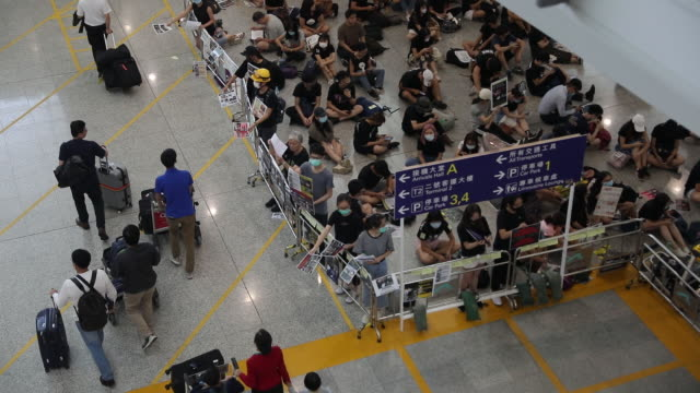 passengers passing protestors at hong kong international airport during hong kong protests hong kong china on tuesday august 13 2019 - flugpassagier stock-videos und b-roll-filmmaterial