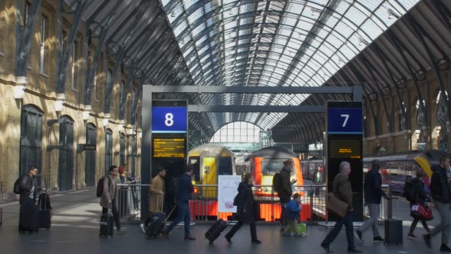 stockvideo's en b-roll-footage met passengers passing through kings cross railway station - perron