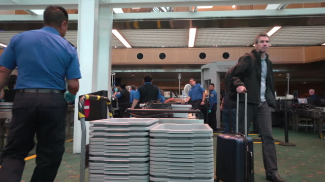 Passengers pick up personal items after clearing TSA security checkpoint inside Portland International Airport