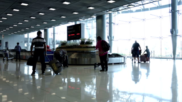 time-lapse passengers picking up their baggage from the carousel at the airport - baggage claim stock videos and b-roll footage