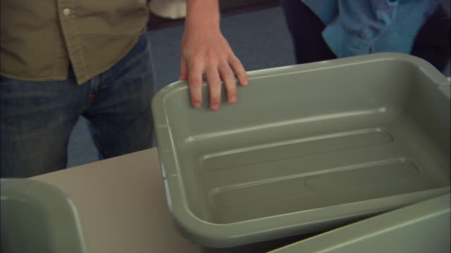 CU SWISH PAN Passengers placing hand luggage in security bins for screening, Ontario, California, USA