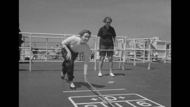 passengers play net game and shuffleboard on top deck of the ss united states as ship sails along / vs shuffleboard, pucks, scoring / passengers... - normandy stock videos & royalty-free footage