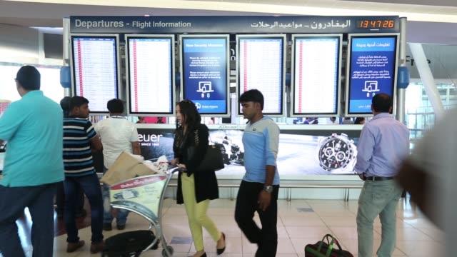 Passengers push luggage through the departures terminal of Dubai International Airport in Dubai United Arab Emirates on Monday Nov 10 A sign reads...