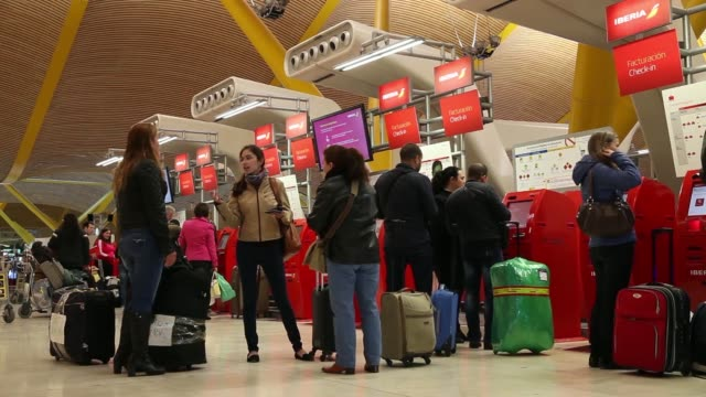 vídeos de stock e filmes b-roll de passengers pushes their luggage across the concourse at madrid barajas airport in madrid, spain, on friday, april 4 passengers walk past flight... - veículo aéreo