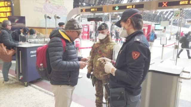 passengers queue up at special checkpoints staffed by soldiers and police at milan's central train station on monday - army video stock e b–roll