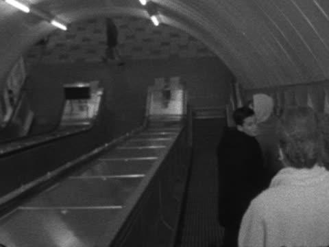 passengers ride an escalator in a london underground tube station - escalator stock videos & royalty-free footage