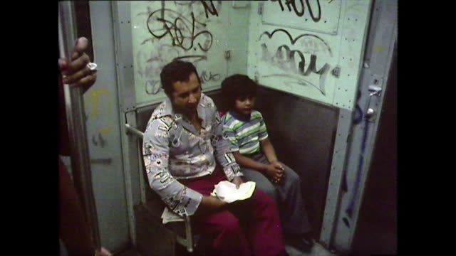 passengers riding in graffitied subway train; new york, 1976 - bbc archive stock-videos und b-roll-filmmaterial