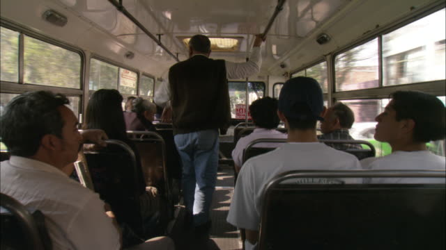passengers sit on a moving bus. - mexico city stock-videos und b-roll-filmmaterial