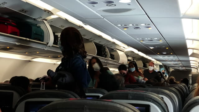 passengers some wearing masks pack onto a nearly full american airlines flight from lax to dallas fort worth international airport during the... - dallas fort worth airport stock videos & royalty-free footage