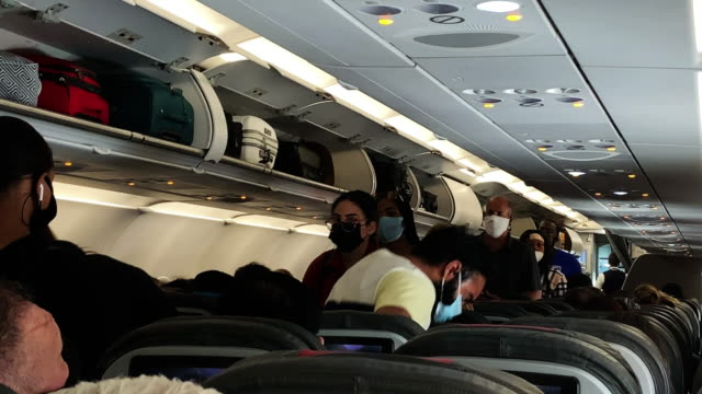 vídeos y material grabado en eventos de stock de passengers, some wearing masks, pack onto a nearly full american airlines flight from lax to dallas fort worth international airport, during the... - avión de pasajeros