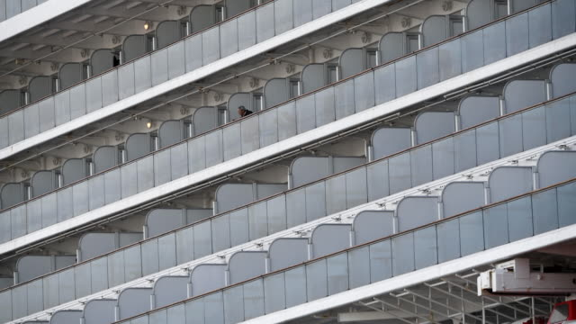 passengers stand on a cabin balcony as he waits onboard the diamond princess cruise ship as it sits docked at daikoku pier where it is being... - aomori prefecture stock videos & royalty-free footage