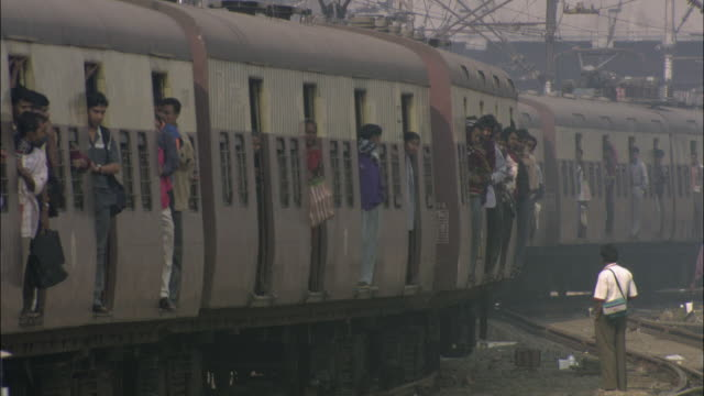 ws passengers standing on train arriving at station under hazy sky / india - smog stock videos & royalty-free footage