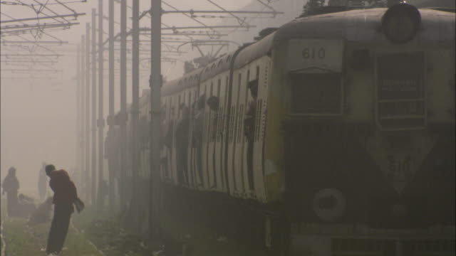 ws passengers standing on train leaving station under hazy sky / india - india video stock e b–roll
