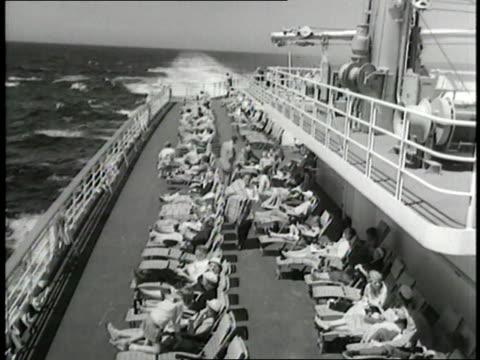 passengers sunbathe on the deck of the ss united states. - passagier stock-videos und b-roll-filmmaterial