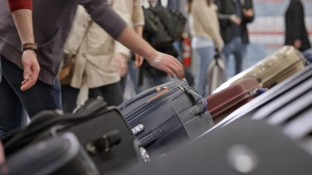 passengers taking their luggage off the baggage carousel at the airport - bagaglio video stock e b–roll