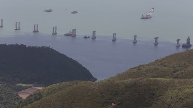 passengers travel in ferry overlooking transport barges sitting near a section of the hong kong zhuhai macau bridge as it stands under construction... - 見渡す点の映像素材/bロール