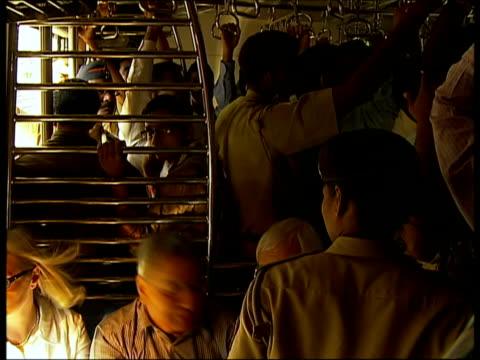 passengers travelling in packed train carriage / mumbai india - アナモルフィック点の映像素材/bロール