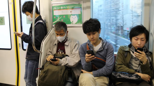 Passengers two of them wearing medical masks checking their smart phones in the moving train