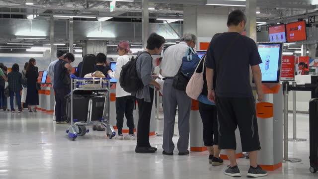 passengers using automated ticket machines at narita airport tokyo japan - flugpassagier stock-videos und b-roll-filmmaterial