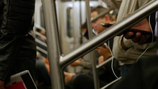 passengers using smart phone on new york subway train - cuffia attrezzatura per l'informazione video stock e b–roll