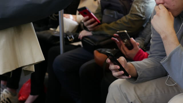 Passengers using smart phone on the New York subway train