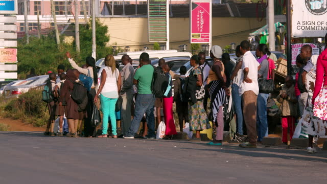 passengers wait for matatus at bus stop ngong road, nairobi, kenya, africa - nairobi stock videos and b-roll footage