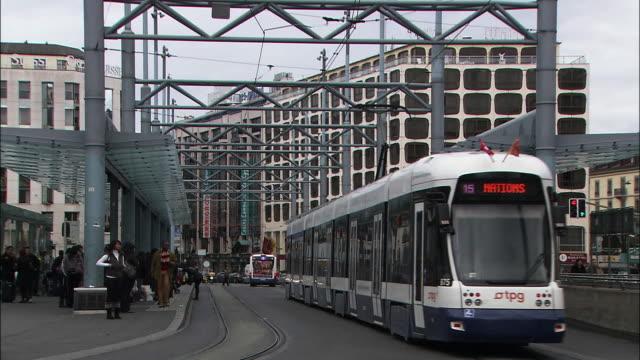Passengers wait on the platform of the Geneva Streetcar Station.