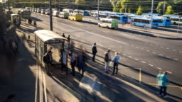 passengers waiting and boarding buses at the bus terminal, time lapse