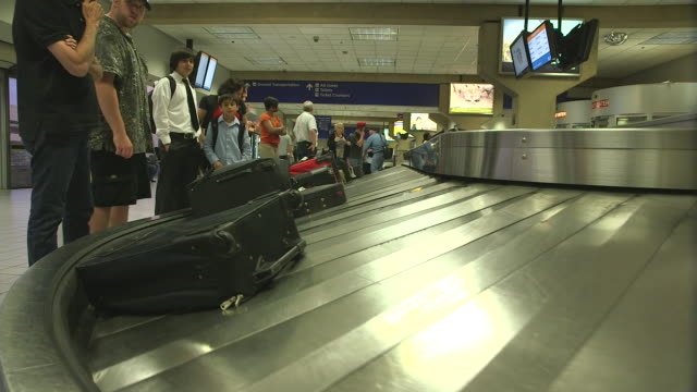 la passengers waiting for baggage on carousel in airport/dfw international airport, dallas-fort worth, texas, usa - dallas fort worth airport stock videos & royalty-free footage