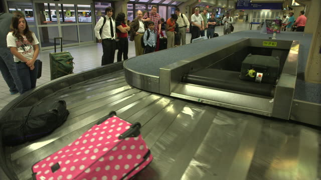 passengers waiting for baggage on carousel in airport/dfw international airport, dallas-fort worth, texas, usa - dallas fort worth airport stock videos & royalty-free footage