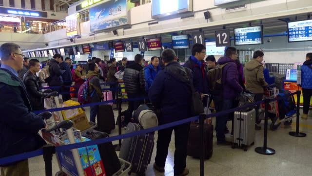 passengers waiting for checked in at airport. - tourist stock videos & royalty-free footage