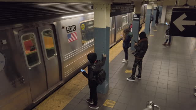 passengers waiting for subway train on platform at 42nd street grand central station. due to massive budget shortfalls due to the covid-19 pandemic,... - underground station platform stock videos & royalty-free footage