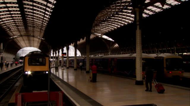 passengers walk along the platform in paddington railway station london. available in hd. - paddington railway station stock videos & royalty-free footage