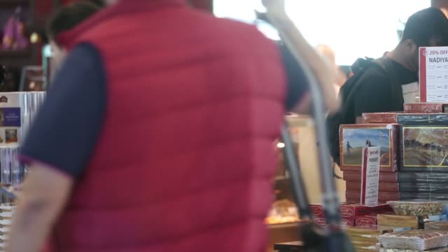 stockvideo's en b-roll-footage met passengers walk past a duty free retail outlet inside dubai international airport in dubai united arab emirates on monday nov 10 a woman looks at... - for sale korte frase